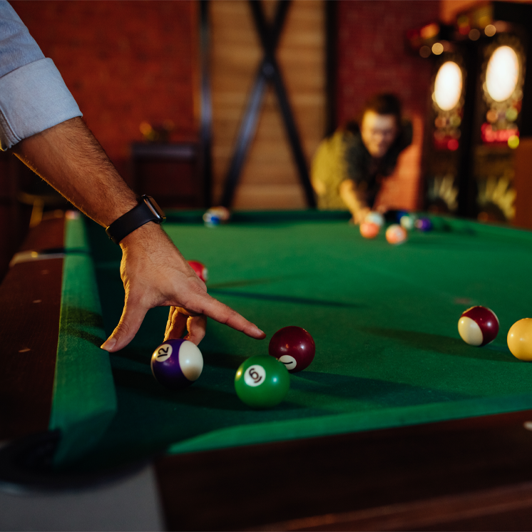 Billiard table in a rec room with people playing pool